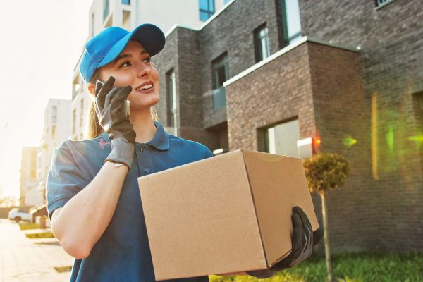 Caucasian young pretty woman, delivery worker in blue hat cap walking the street, carrying cardbox parcel and talking on mobile phone. Female beautiful courier with carton box speaking on cellphone.